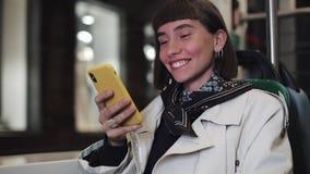 公共交通工具的可爱的微笑的年轻女人使用一个手机 她是发短信,检查邮件,闲谈或 股票视频
