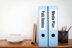 公共关系和媒体计划黏合剂在办公室 在一个木架子的文具 免版税库存照片