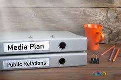 公共关系和媒体计划-在木办公桌上的两个文件夹 库存图片