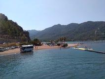 公共汽车、海、天空和游人在水中在女孩沙子靠岸 这著名浅滩,游人朝圣地方  免版税库存图片