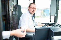 公共汽车司机在公共汽车上的卖票 免版税库存照片