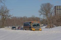 公共汽车和汽车在路thourgh雪 免版税图库摄影