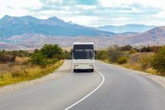 公共汽车在一个山区继续前进一条乡下公路 免版税库存照片