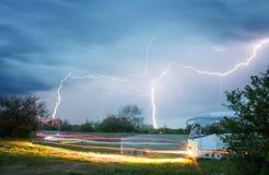 公共汽车在驾驶反对一道风雨如磐的天空和闪电的背景的乡下 免版税库存图片
