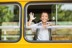 从公共汽车的微笑的男小学生挥动的手 免版税库存图片