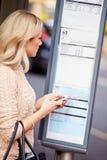 公共汽车站的妇女与手机读书时间表 免版税库存图片
