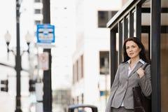 公共汽车站等待的妇女 免版税库存照片