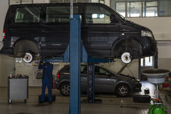 公共汽车,汽车在一个水力插座上升了 停止修理,轮胎变动 免版税图库摄影