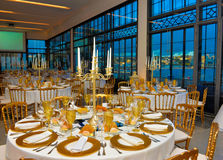 公司事件制表金黄装饰,晚餐会有海景,演讲宴会 免版税库存图片