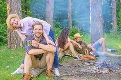 公司朋友夫妇或家庭喜欢一起放松放松在营火附近的森林朋友在远足的天以后或 图库摄影