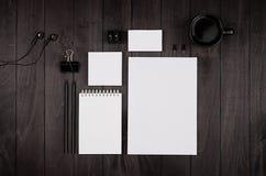 公司本体模板,空白的文具设置了用咖啡和耳机在黑时髦的木背景 免版税库存图片
