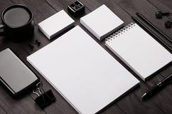 公司本体模板,空白的文具设置了用咖啡和耳机在黑时髦的木背景 库存照片