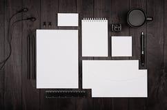 公司本体模板,空白的文具设置了用咖啡和耳机在黑时髦的木背景 库存图片
