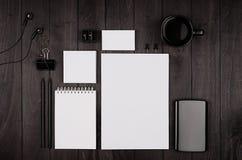 公司本体模板,空白的文具设置了用咖啡和耳机在黑时髦的木背景 免版税库存照片