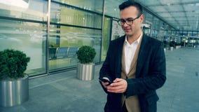 公司男性经理步行和类型在电话,微笑,关闭  股票录像