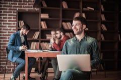 公司的雇员坐与膝上型计算机的一把椅子在backg 免版税库存图片