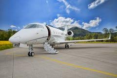 公司私人喷气式飞机-飞行在山的跑道 免版税库存图片