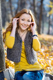 公园听的音乐的年轻俏丽的妇女 图库摄影