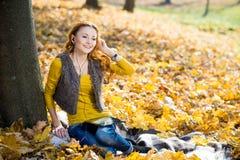 公园听的音乐的年轻俏丽的妇女 免版税库存照片