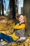 公园听的音乐的年轻俏丽的妇女 免版税库存图片