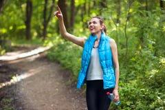 公园的愉快的赛跑者年轻女人,森林,当一个瓶水,指向某事  蓝色无袖的夹克 体育运动 库存照片