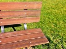 公园长椅和绿草与阴影 库存照片