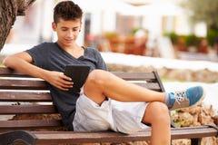 公园长椅的十几岁的男孩使用数字式片剂 库存照片