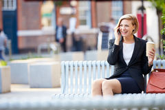 公园长椅的女实业家用使用手机的咖啡 免版税库存照片