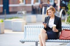 公园长椅的女实业家用使用手机的咖啡 免版税库存图片