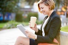 公园长椅的女实业家用使用数字式片剂的咖啡 库存图片
