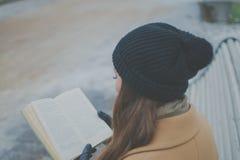 公园长椅的美丽的女孩读书的 免版税库存图片