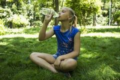 公园饮用水的年轻十几岁的女孩 免版税库存图片