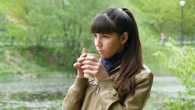 公园水杯的美丽的女孩从一次性杯子的外带的咖啡 有吸引力的woma画象  股票视频