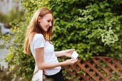 公园iwith智能手机的女孩 免版税库存照片