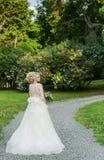 公园whith婚礼的美丽的白肤金发的新娘 免版税图库摄影