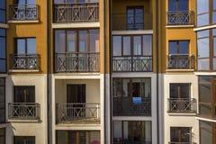 公寓或办公楼细节外墙  伪造的阳台栏杆,天空蔚蓝在发光的镜子窗口里反射了 库存图片