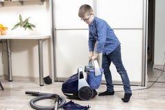 公寓清洁 男孩放一个容器水入吸尘器 库存图片