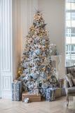 公寓用一棵圣诞树装饰,在树下是礼物 免版税库存照片