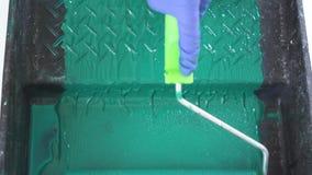 公寓的修理-滚动的绿色漆滚筒油漆容器特写镜头 股票录像