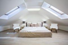 公寓的明亮的顶楼卧室 免版税库存图片