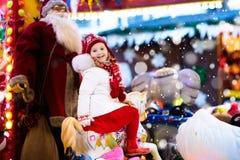 公平的圣诞节的孩子 乘坐Xmas转盘的孩子 库存照片