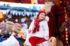 公平的圣诞节的孩子 乘坐Xmas转盘的孩子 库存图片