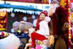 公平的圣诞节的孩子 乘坐Xmas转盘的孩子 免版税库存图片