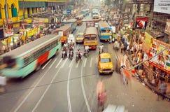 从公开公共汽车、汽车和冲的人的行动迷离有许多的印地安路的商店 免版税库存照片