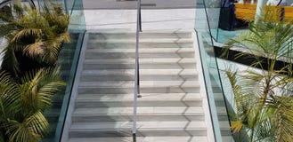 公开楼梯楼梯和镀铬物金属化与安全玻璃边部分的扶手栏杆分切器 免版税库存图片