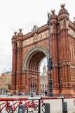 公开自行车系统在凯旋门旁边骑自行车在巴塞罗那 库存图片