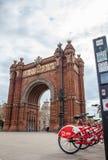 公开自行车系统在凯旋门旁边骑自行车在巴塞罗那 免版税库存图片