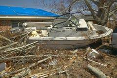 公羊堵塞在房子前面的小船和残骸 免版税库存图片