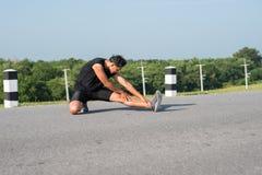 公赛跑者舒展腿肌肉为奔跑做准备 库存照片