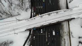 公路交叉点与汽车、公共汽车和其他交通的冬时鸟瞰图与在路上的铁路桥 影视素材